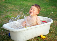 A happy baby bathed in the bath and playing with toys. Stock Image