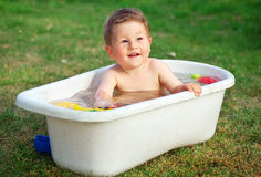 A happy baby bathed in the bath and playing with toys. Royalty Free Stock Photography