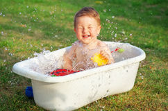 A happy baby bathed in the bath and playing with toys Stock Photo