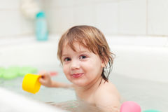 Happy baby bathes in bathtub Royalty Free Stock Image