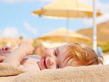 Happy baby on the beach sunbed. Stock Images