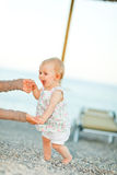 Happy baby on beach trying to start walking. Happy baby on the beach trying to start walking with mothers help Royalty Free Stock Photos