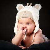 Happy baby in bear cap. Sucks a finger Stock Photos