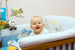 Happy baby in bed. Six month happy baby sitting in bed and smiling Royalty Free Stock Photos