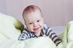 Happy baby in bed on his Royalty Free Stock Images