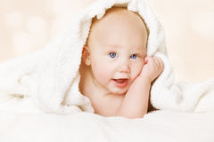 Happy Baby in Bed, Kid under Towel, Cute Infant Boy. Looking at camera Royalty Free Stock Photo
