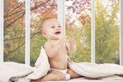 Happy baby on bedroom laughing alone Stock Images