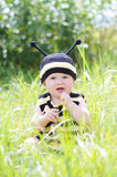 Happy baby in bee costume tastes grass on the meadow Royalty Free Stock Photos
