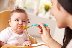 Happy Baby Being Fed In High Chair At Meal Time Stock Photo
