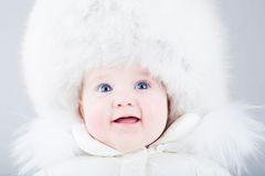 Happy baby in big fur hat and white snow jacket Royalty Free Stock Photos