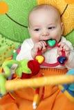 Happy baby bites rattle Royalty Free Stock Image