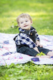 Happy baby on blanket. Smiling baby boy on blanket in grass Stock Photography