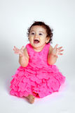 Happy Baby Blowing Kisses. A happy and beautiful baby sits on a white background and blows kisses with hands out. She looks like she could be clapping royalty free stock image