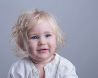 Happy baby blue eyes blonde. Long hair gray background royalty free stock images
