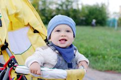Happy baby boy age of 11 months on baby carriage outdoors Stock Image