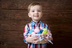 Happy baby boy with a basket of easter eggs on wooden background.  stock image