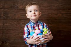 Happy baby boy with a basket of easter eggs on wooden background royalty free stock photography