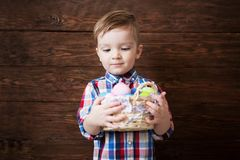 Happy baby boy with a basket of eggs on wooden wall background stock photos