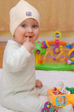 Happy baby boy biting his finger. And playing with toys Stock Image