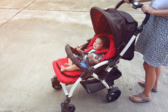 Happy baby boy cute in child stroller seat on wheel Royalty Free Stock Photography