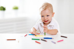 Happy baby boy draws with colored pencils. And laughs Stock Photo