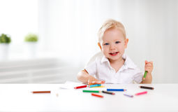 Happy baby boy draws with colored pencils Royalty Free Stock Images