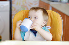 Happy baby boy drink from baby cup. Happy baby boy age of 1 year drink from baby cup Royalty Free Stock Photo