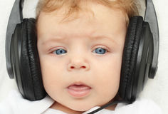 Happy baby boy in earphones Stock Photography
