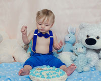 Happy baby boy eating cake for his first birthday party. Happy baby boy eating cake by hands and feet for his first birthday party. Handsome little gentleman Stock Photos