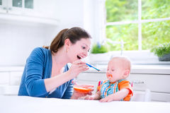 Happy baby boy eating first solid food witn his mother. Young attractive mother feeding her cute baby son, giving him his first solid food, healthy vegetable Stock Images