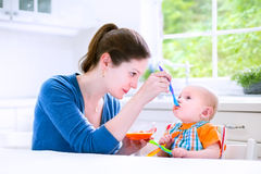 Happy baby boy eating his first solid food witn his mother. Young attractive mother feeding her cute baby son, giving him his first solid food, healthy vegetable Stock Image