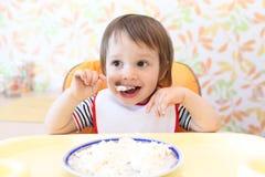Happy baby boy eating quark Stock Photography