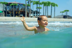 Happy baby boy enjoys swimming in sea waves Stock Photo