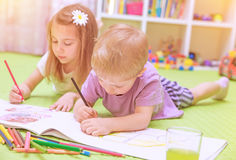 Happy baby boy & girl enjoying homework Royalty Free Stock Photography