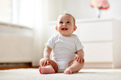 Happy baby boy or girl sitting on floor at home Royalty Free Stock Photography