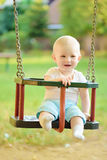 Happy baby boy having fun on a swing ride at a playground Royalty Free Stock Photo