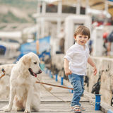 Happy baby boy with him dog on berth in summer Royalty Free Stock Photography