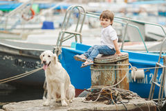 Happy baby boy with him dog on berth in summer Royalty Free Stock Photo