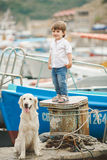 Happy baby boy with him dog on berth in summer Stock Images