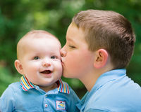 Happy baby boy kissed by his brother stock photography