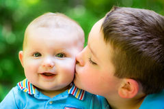 Happy baby boy kissed by his brother stock image