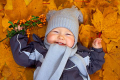 Happy baby boy lies among fallen leaves Royalty Free Stock Images