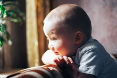Happy baby boy looking at window waiting. Little, cheerful two years old boy looking out the window and thinking and waiting for something Stock Photos