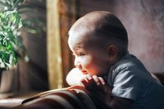 Happy baby boy looking at window waiting. Little, cheerful two years old boy looking out the window and thinking and waiting for something. Sun shine Stock Photo