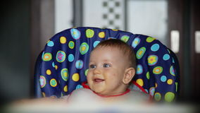 Happy baby boy at lunch time Stock Images