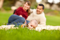 Happy Baby Boy and Mixed Race Parents Playing in the Park Royalty Free Stock Image