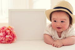 Happy baby boy with photo frame and flower Stock Photo