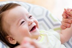 Happy baby boy playing with his parent. In his house Stock Image