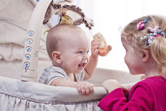 Happy baby boy playing with his sister Royalty Free Stock Image