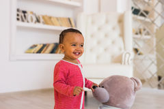 Happy baby boy playing with his teddy bear.  Stock Photos